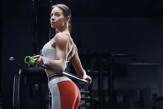 Mulher de aptidão atlética no treino no ginásio com barra de corpo, alongamento dos músculos. conceito de fitness e esporte. fisiculturista caucasiana fazendo exercícios abdominais na academia