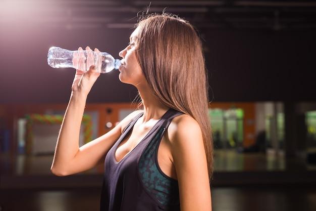 Mulher de aptidão bebendo água de garrafa. mulher jovem e musculosa no ginásio, fazendo uma pausa do treino.