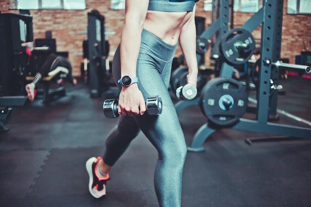 Mulher de aptidão com corpo de esportes exercitar com halteres no ginásio. pulmões com halteres. conceito de treinamento