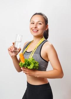 Mulher de aptidão com legumes frescos e um copo de água