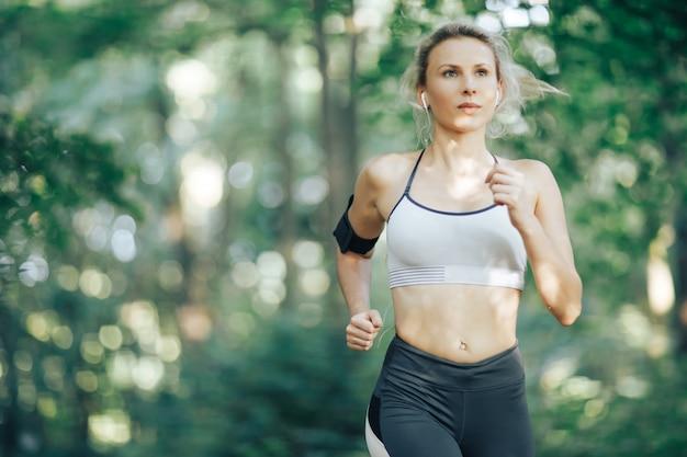 Mulher de aptidão correndo no parque de manhã