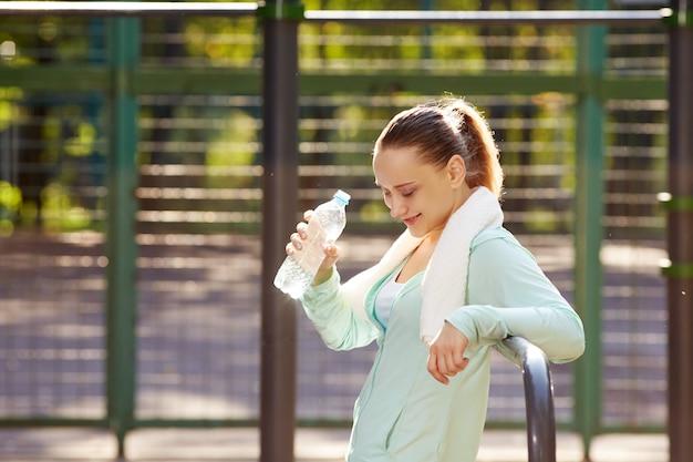 Mulher de aptidão descansando depois de treino, relaxante, bebendo água limpa da área de fitness ao ar livre de garrafa em um parque