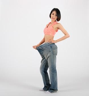 Mulher de aptidão desportiva em jeans soltos depois de perder peso em branco