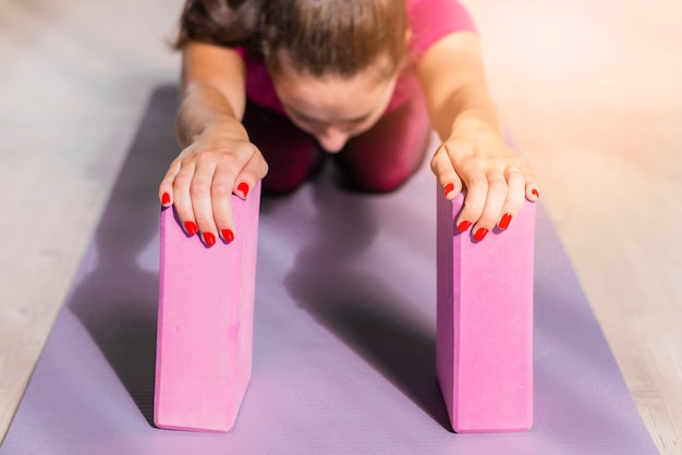 Mulher de aptidão desportiva praticando ioga com blocos-de-rosa na esteira de exercícios