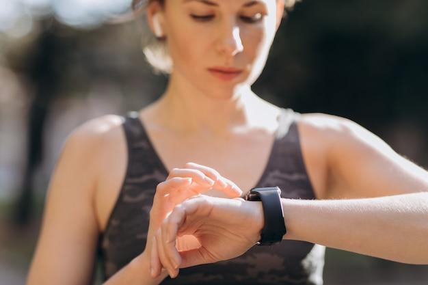 Mulher de aptidão em fones de ouvido sem fio usando smartwatch