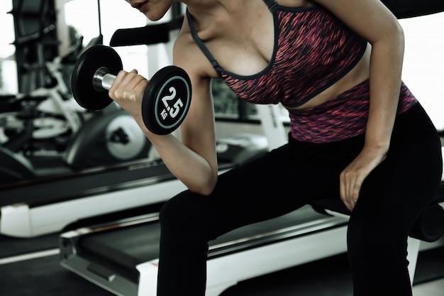 Mulher de aptidão em treinamento. abs forte mostrando de manhã. na academia