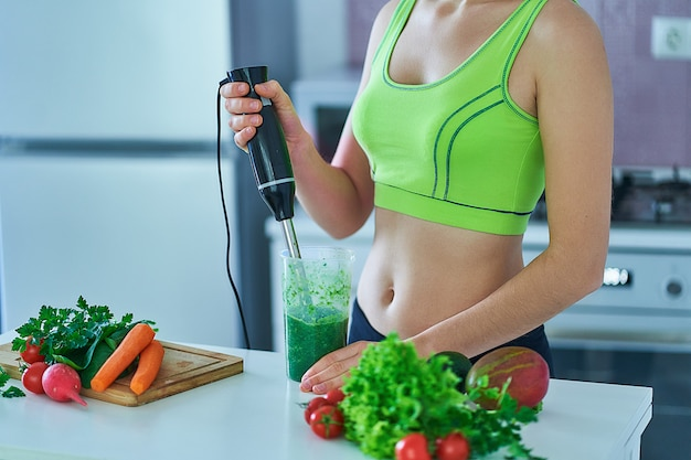 Mulher de aptidão esportiva no sportswear prepara um smoothie verde usando um liquidificador na cozinha