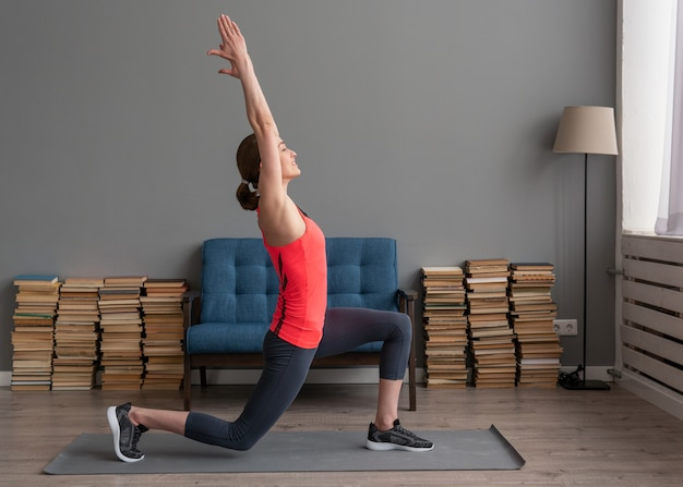Mulher de aptidão fazendo frente estocada exercício para alongamento de perna na esteira em casa