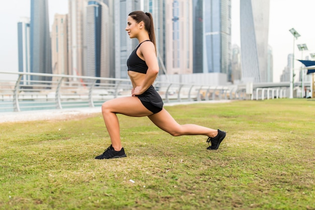 Mulher de aptidão fazendo lunges exercícios para glúteo e perna músculo treino treino núcleo músculos, equilíbrio, cardio e estabilidade na frente de arranha-céus