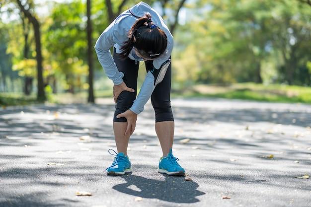 Mulher de aptidão jovem segurando sua lesão na perna de esportes, músculo doloroso durante o treinamento
