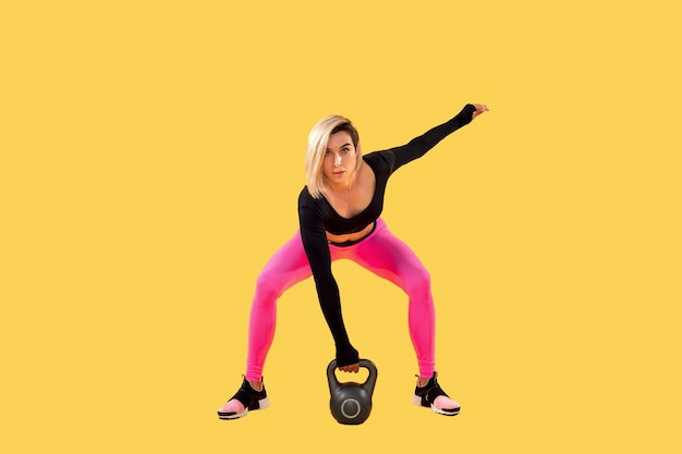 Mulher de aptidão no sportswear rosa e preto elegante malhar com kettlebell na parede amarela. força e motivação.