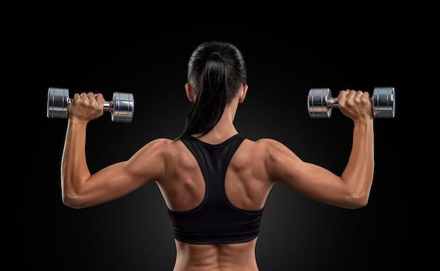 Mulher de aptidão nos músculos das costas com halteres de treinamento