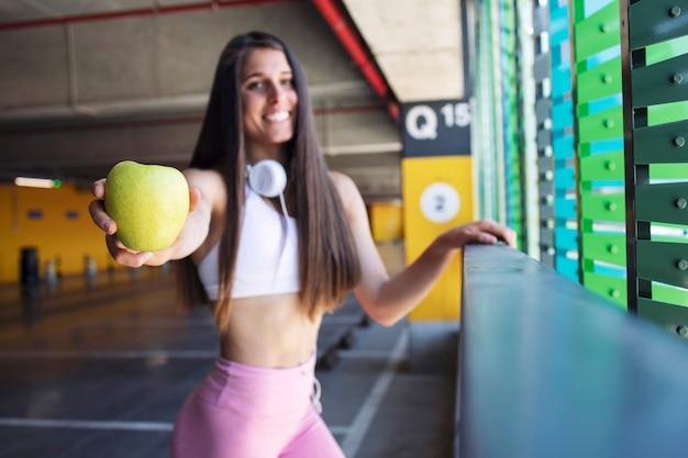 Mulher de aptidão segurando uma fruta orgânica de maçã após o treino.