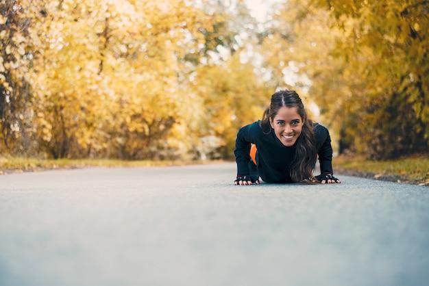 Mulher de aptidão sorridente fazendo flexões no parque da cidade.