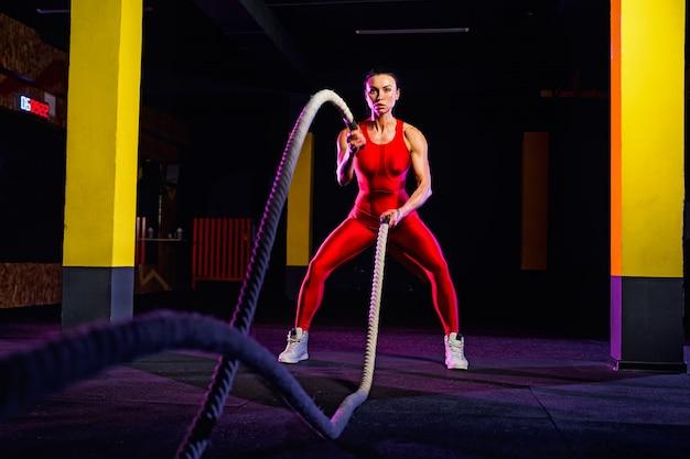 Mulher de aptidão usando cordas de treinamento para o exercício no ginásio. atleta malhando com cordas de batalha no ginásio cruz
