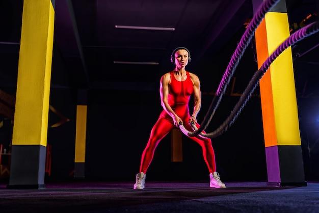 Mulher de aptidão usando cordas de treinamento para o exercício no ginásio. atleta malhando com cordas de batalha no ginásio