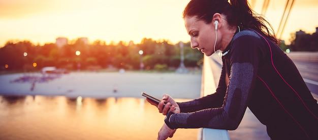 Mulher de aptidão usando telefone inteligente