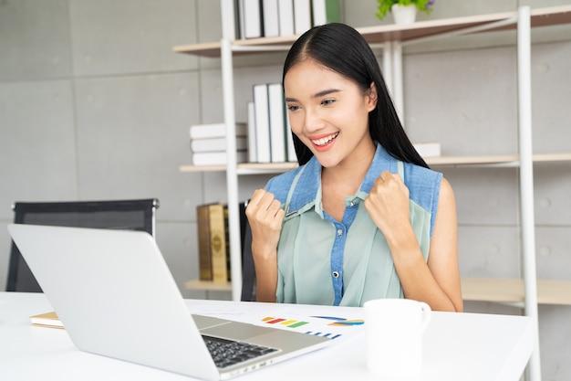Mulher de ásia com laptop comemorando o conceito de sucesso