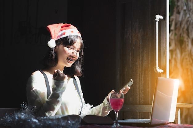 Mulher de ásia do close up, chapéu adolescente do natal do desgaste da menina usando o smartphone com feliz.