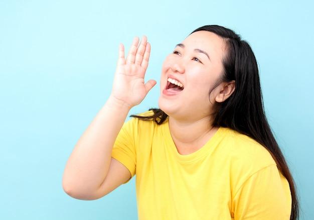 Mulher de ásia do retrato que grita e mão em sua boca, isolada no fundo azul no estúdio.