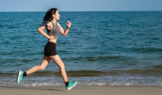 Mulher de ásia em mercadorias do esporte que exercitam e que correm na praia.