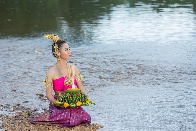 Mulher de ásia em vestido tailandês tradicional segurar kratong. festival loy krathong