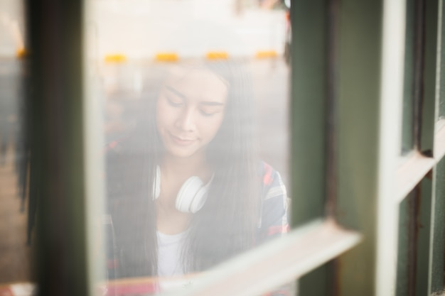 Mulher de ásia que escuta a música com feliz dentro da cafetaria.