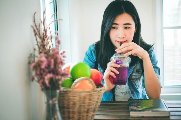 Mulher de ásia que lê um livro e que bebe um suco na cafetaria.