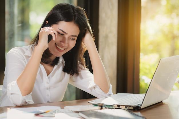 Mulher de ásia que usa o smartphone, computador pessoal que trabalha com feliz.