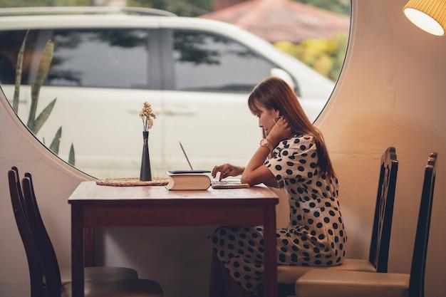 Mulher de ásia, usando o computador portátil, trabalhando no tempo livre com feliz