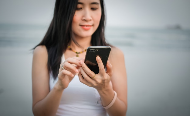 Mulher de ásia, usando telefone celular para verificar a mídia social