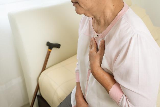 Mulher de ataque cardíaco, segurando o peito no quarto da cama, problema de saúde do conceito sênior