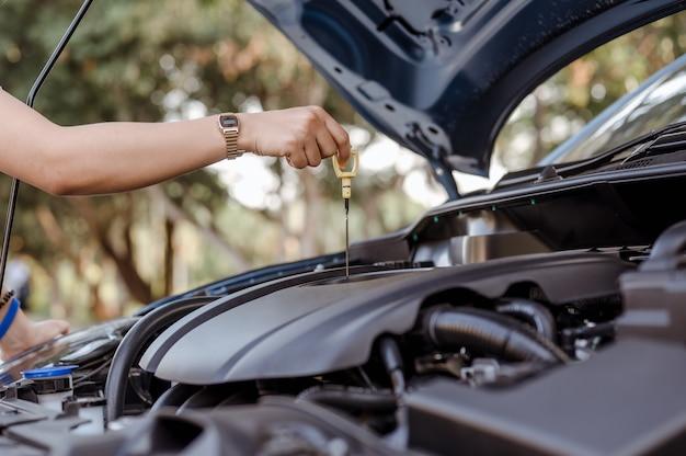Mulher de autoatendimento usa vareta de nível de óleo para verificar o nível de óleo do motor, manutenção e reparos