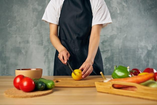 Mulher de avental preto almoçando em casa comida vegetariana dieta dieta