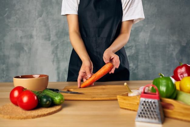 Mulher de avental preto almoçando em casa tábua de comida vegetariana