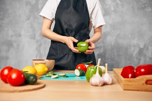 Mulher de avental preto cozinhando dieta alimentar saudável