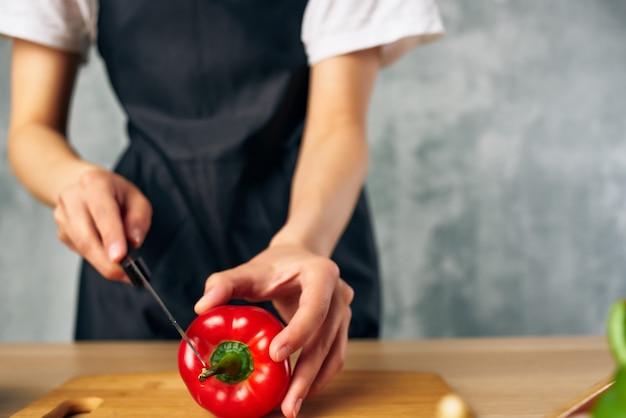 Mulher de avental preto cozinhando uma tábua de alimentação saudável