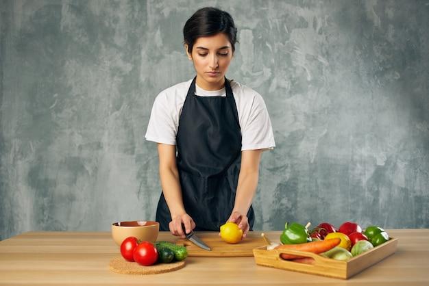 Mulher de avental preto no fundo isolado de legumes de corte de cozinha. foto de alta qualidade