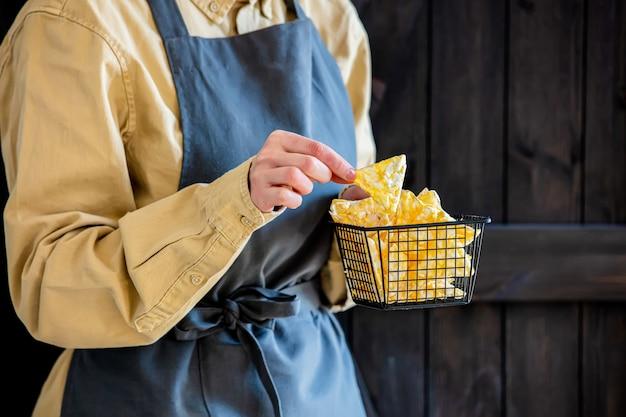 Mulher de avental segura batatas fritas veganas