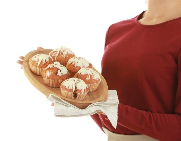 Mulher de avental segurando o prato com muffins no fundo branco
