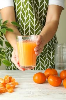 Mulher de avental segurando um copo com suco de tangerina