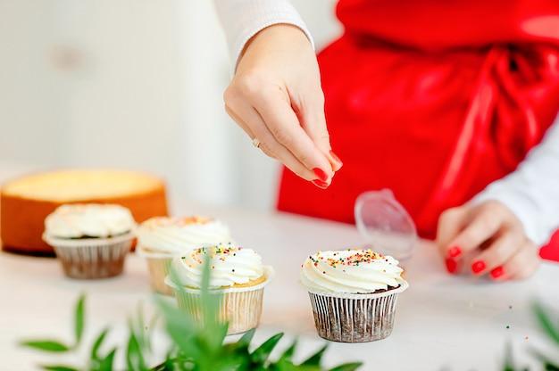 Mulher de avental vermelho decora com cupcakes granulados coloridos na cozinha em casa.