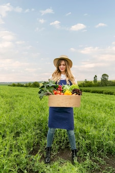 Mulher de baixo ângulo com cesta de legumes