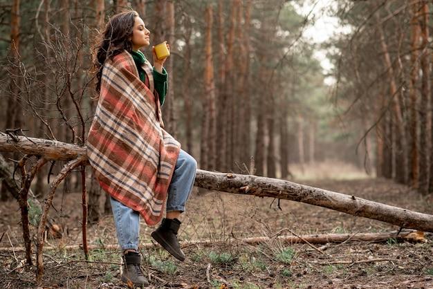 Mulher de baixo ângulo, desfrutando de uma xícara de chá na natureza