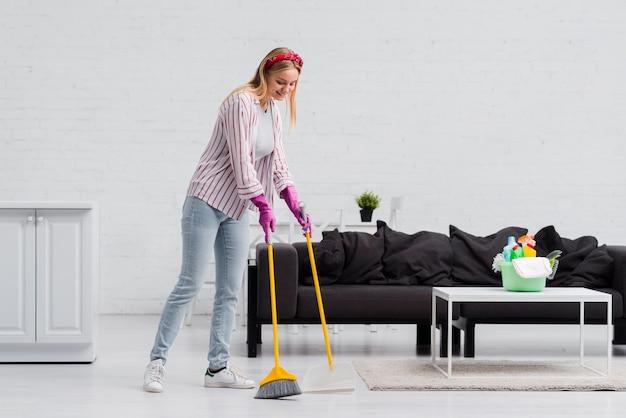 Mulher de baixo ângulo escovando o chão