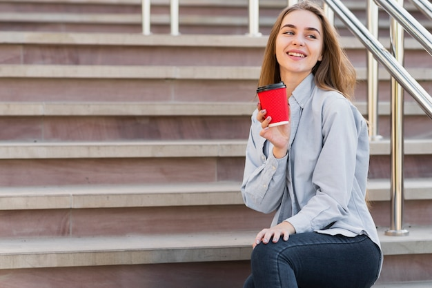 Mulher de baixo ângulo nas escadas, bebendo café