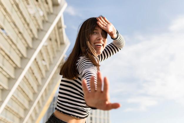 Mulher de baixo ângulo, olhando feliz ao ar livre