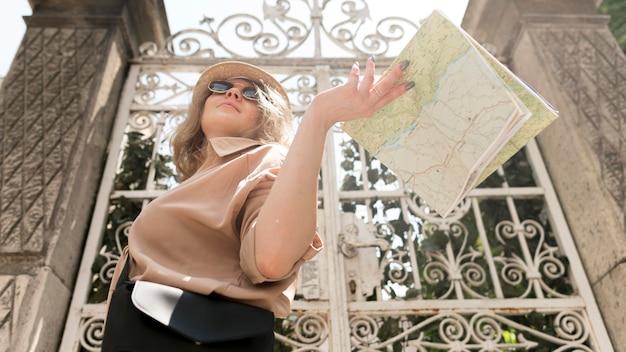 Mulher de baixo ângulo, segurando o mapa