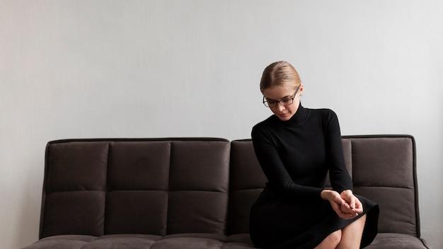 Mulher de baixo ângulo, sentada no sofá