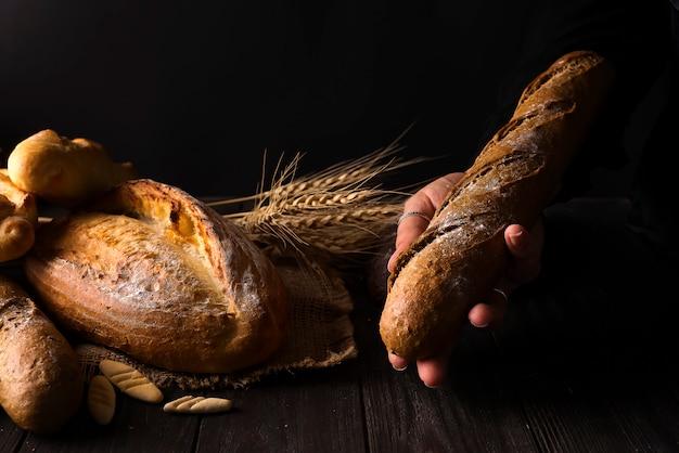 Mulher de baker, segurando o pão orgânico rústico de pão nas mãos